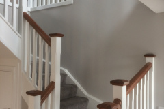 White-closed-string-stairs-with-mahogany-handrail-mahogany-newel-caps-with-chamfered-corners